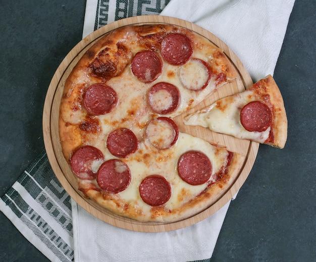 Pizza pepperoni ze stopionym białym serem na wierzchu.