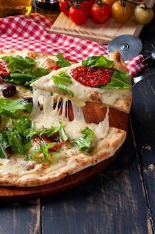 Pizza po brazylijsku z mozzarellą, suszonymi pomidorami i rukolą. ktoś bierze kawałek i rozciąga ser