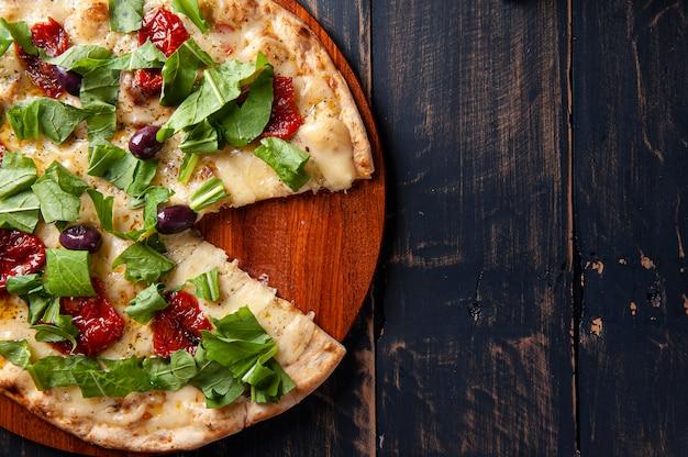 Pizza po brazylijsku z mozzarellą, suszonymi pomidorami i rukolą. widok z góry. skopiuj miejsce