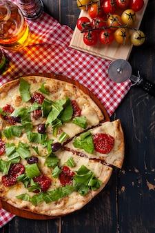 Pizza po brazylijsku z mozzarellą, suszonymi pomidorami i rukolą. widok z góry.