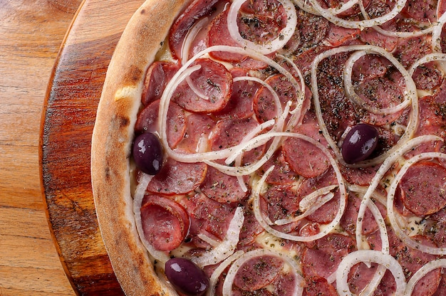 Pizza po brazylijsku z serem mozzarella, kiełbasą pepperoni i cebulą. widok z góry