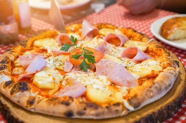 Pizza podawana na drewnianej tacy / domowy ser do pizzy z szynką na stole jadalnym potrawy kuchni włoskiej