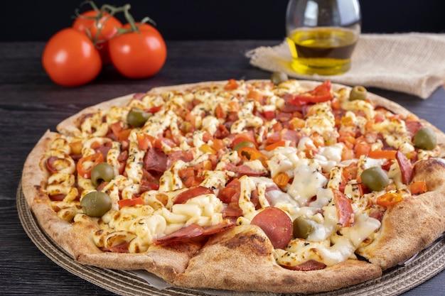 Pizza polana sosem pomidorowym, serem catupiry, plasterkami pepperoni, pomidorem pokrojonym w kostkę i papryczką chili.