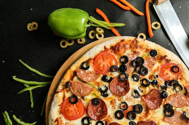 Pizza salami oliwki ser pomidor papryka widok z boku