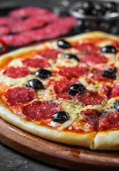 Pizza salami z oliwkami na ciemnej powierzchni