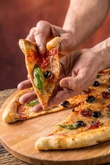 Pizza. smaczna świeża włoska pizza na starym drewnianym stole. kawałek pizzy w dłoni człowieka.