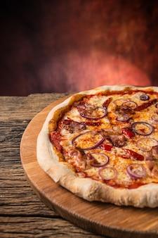 Pizza. smaczna świeża włoska pizza z papryką cihili bekon i cebulą na starym drewnianym stole.