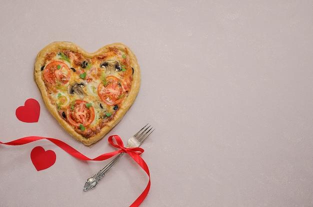 Pizza w formie serca na beżowym stole z czerwonymi serduszkami z widelcem z czerwoną wstążką. zamów pizzę na romantyczną kolację w walentynki. miłość.