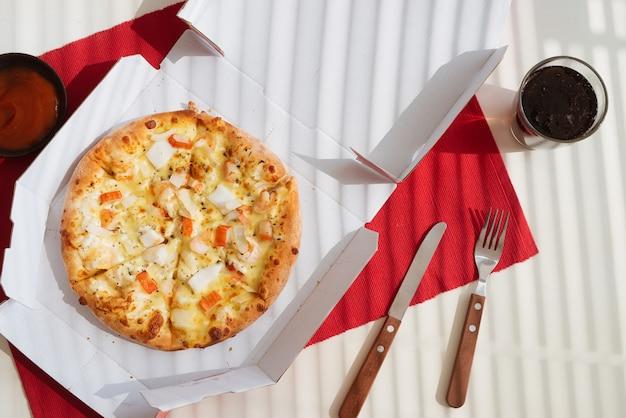Pizza w kartonowym pudełku na białym stole. dostawa pizzy. menu pizzy.