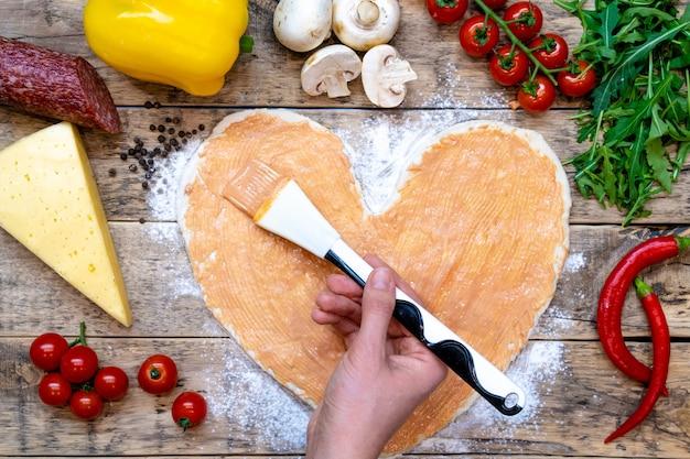Pizza w kształcie serca i składniki na walentynki, proces gotowania