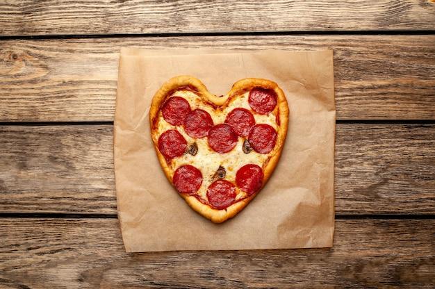 Pizza w kształcie serca na drewnianym stole