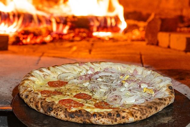 Pizza w stylu brazylijskim wchodząca do pieca opalanego drewnem. selektywne skupienie