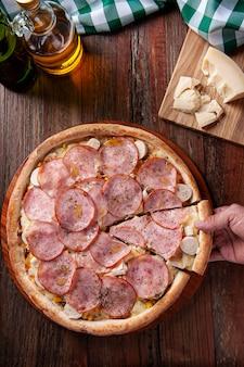 Pizza w stylu brazylijskim z polędwicą wołową z mozzarellą, sercami palmowymi i kukurydzą. ktoś bierze kawałek ręcznie. widok z góry