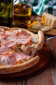 Pizza w stylu brazylijskim z polędwicą wołową z mozzarellą, sercami palmowymi i kukurydzą. wyjmowanie kawałka i rozciąganie sera