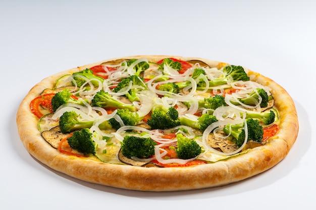 Pizza wegetariańska z sosem pomidorowym, brokułami, pomidorami, cukinią, bakłażanem i krążkami cebulowymi. pizza brazylijska.