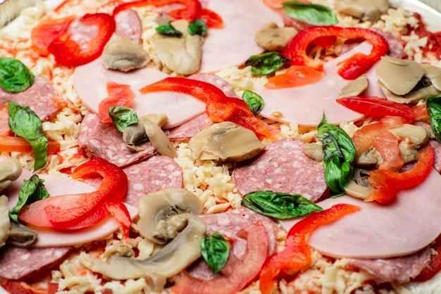 Pizza z bliska. boczek, salami, pieczarki i zielenina.