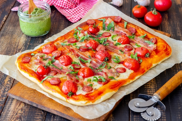 Pizza z boczkiem, kiełbasą, mozzarellą, pomidorami i bazylią. kuchnia włoska. przepis.