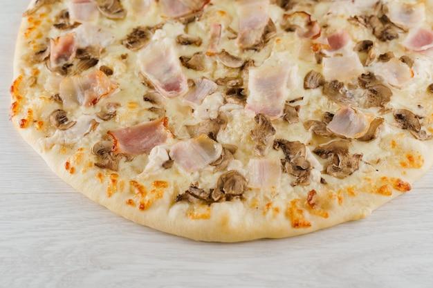 Pizza z boczkiem, pieczarkami i serem na białym tle na białej powierzchni drewnianych
