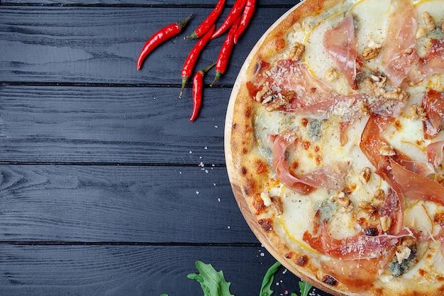 Pizza z jamon, gorgonzola i parmezanem, orzechami i gruszką. widok z góry. świeża domowa włoska pizza. tło żywności pizza z mięsem i serem na ciemnym drewnianym tle