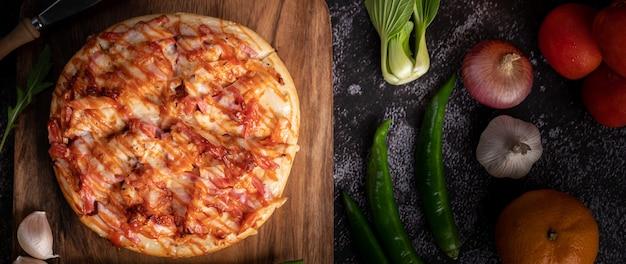 Pizza z kiełbasą, kukurydzą, fasolą, krewetkami i boczkiem na drewnianym talerzu