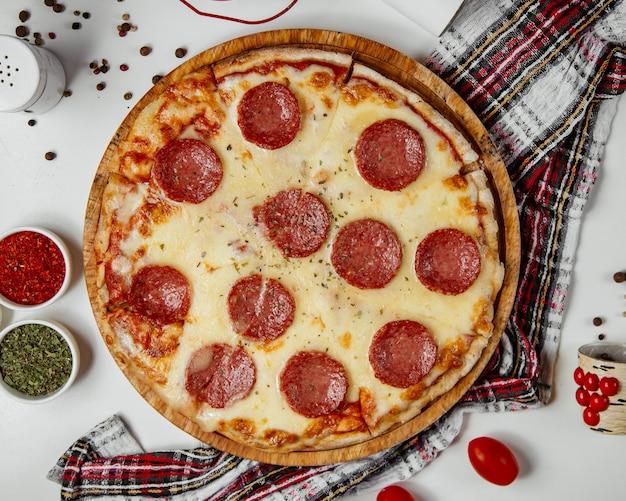Pizza z kiełbasą podawana z suszonymi ziołami
