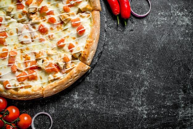 Pizza z kurczakiem i sosem serowym. na ciemnym tle rustykalnym