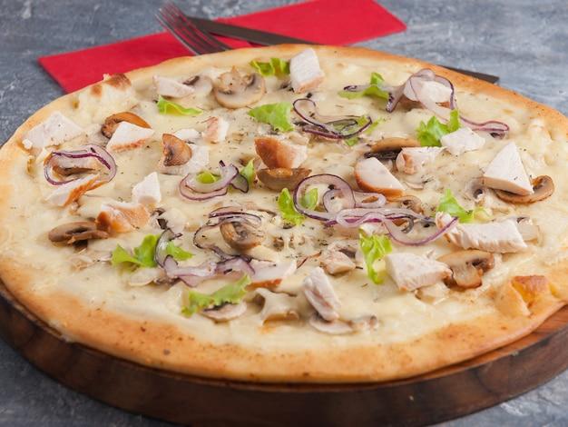 Pizza z kurczakiem, pieczarkami i czerwoną cebulą na drewnianej desce