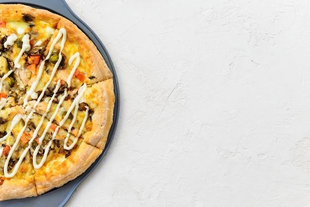 Pizza z kurczakiem, pomidorami, papryką, serem i sosem na jasnym tle. orientacja pozioma, widok z góry, miejsce na kopię.