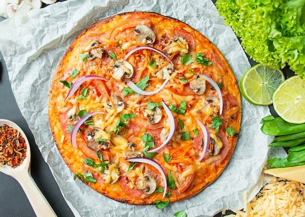 Pizza z kurczakiem, serem i pieczarkami na ciemnym tle. widok z góry. skopiuj miejsce.