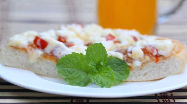 Pizza z liśćmi mięty z bliska na białym tle