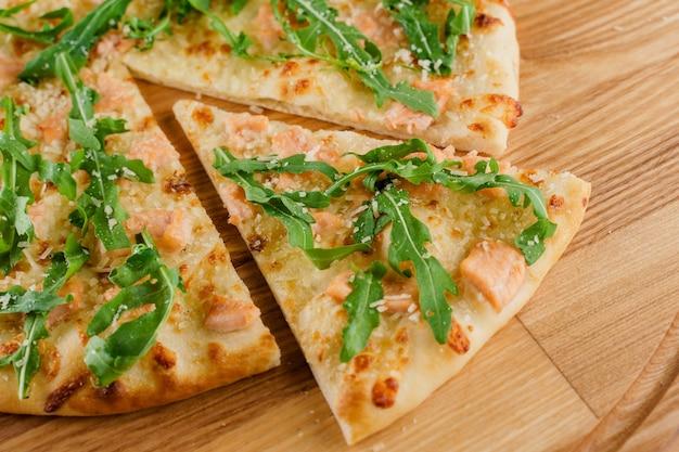 Pizza z łososiem, parmezanem i rukolą na białym tle na białej powierzchni drewnianych