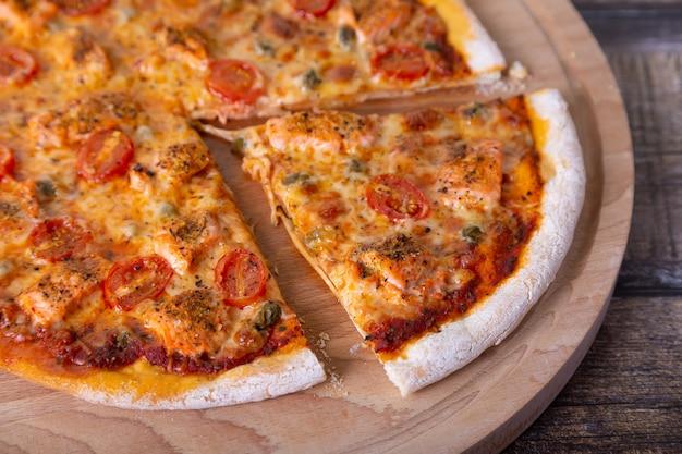 Pizza z łososiem, pomidorami i kaparami na drewnianej desce. cała pizza, jeden kawałek odcięty. zbliżenie.