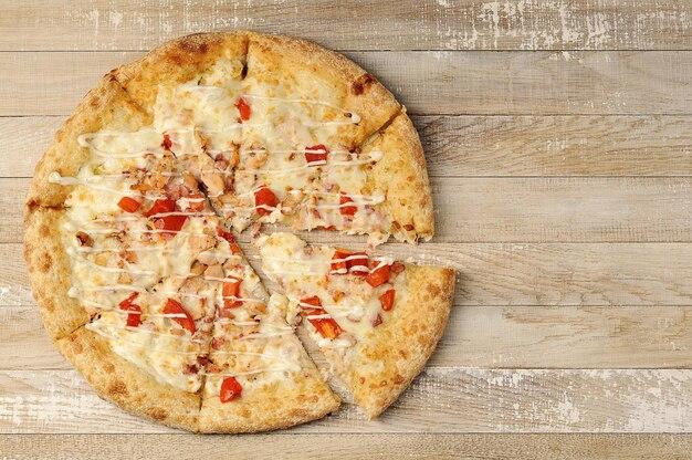 Pizza z mięsem i pomidorami na powierzchni drewna