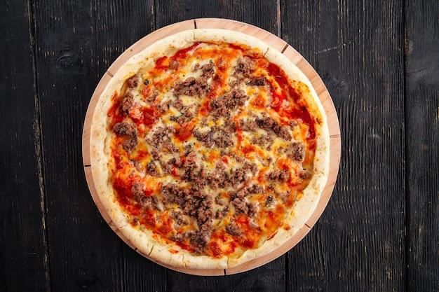 Pizza z mięsem mielonym i sosem pomidorowym na ciemnym drewnianym stole