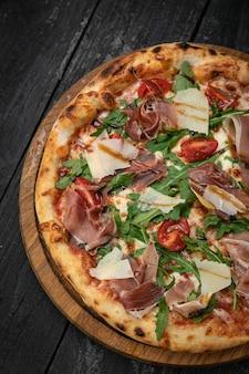 Pizza z mięsnym parmezanem i pomidorami na drewnianej desce na ciemnym stole