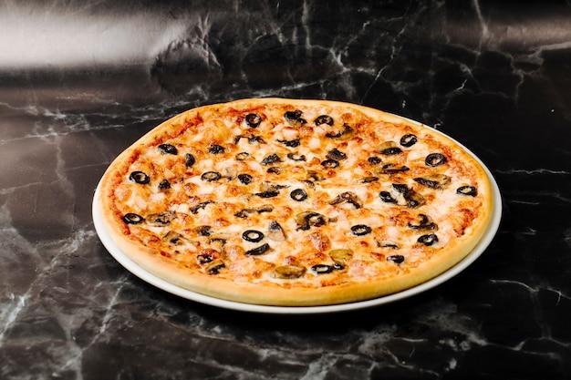 Pizza z mieszanymi składnikami i czarnymi rolkami oliwek.