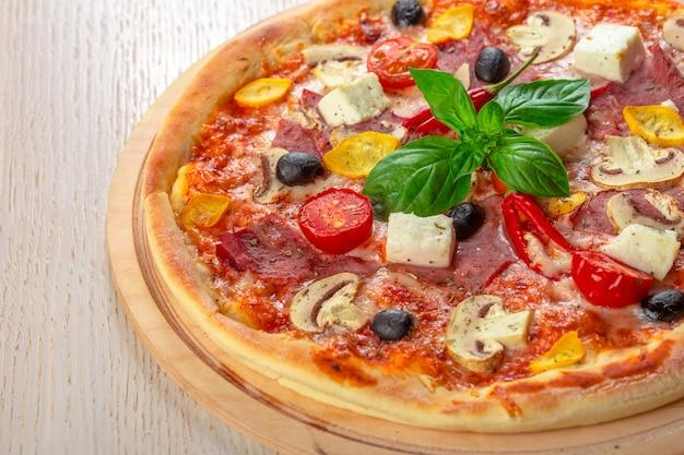 Pizza z mozzarellą, szynką, pomidorami wiśniowymi, czarnymi oliwkami