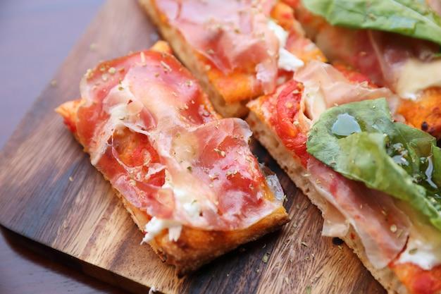 Pizza z parma baleronu sałatkową rakietą i parmesan na ciemnym drewnianym tła zakończeniu up. włoskie jedzenie