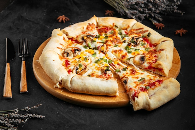 Pizza z pieczarkami i warzywami na ciemnym drewnianym stole