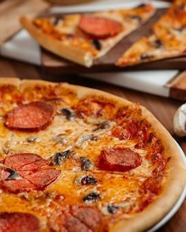 Pizza z plasterkami pepperoni i czarnymi oliwkami