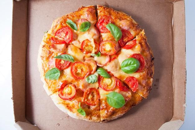 Pizza z pomidorami, kiełbaskami i serem w kartoniku