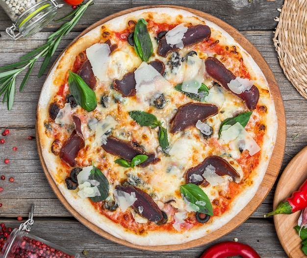 Pizza z pomidorami, mozzarellą, czarnymi oliwkami i bazylią. wyśmienicie włoska pizza na drewnianej pizzy desce. widok z góry stołu