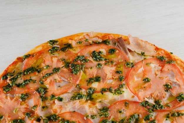 Pizza z pomidorami, serem, mięsem, sosem bazyliowym na białym tle na białej powierzchni drewnianych