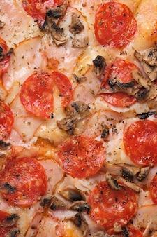 Pizza z pomidorami szynka pikantne pieczarki kalbasa ser mozzarella przyprawy i sos pomidorowy