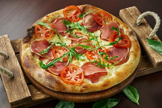 Pizza z prosciutto di parma, rukolą, białym sosem i pomidorami na drewnianej tacy.