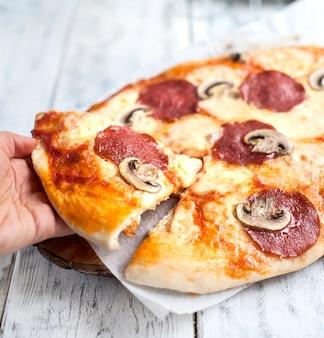 Pizza z salami i grzybami na białym tle drewnianych i dwie szklanki białego wina