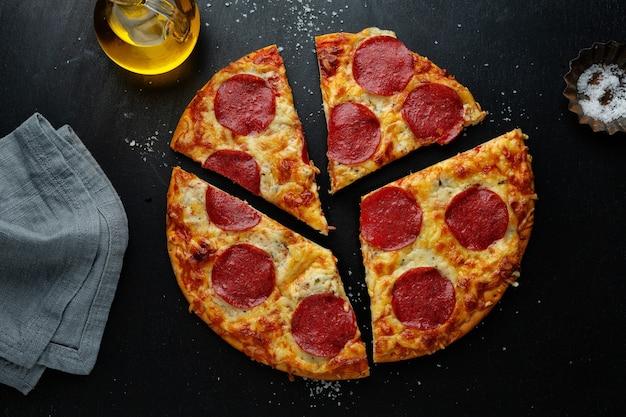 Pizza z salami i serem na pudełku po pizzy na ciemnym stole.