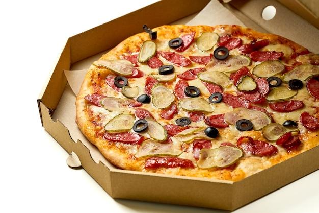 Pizza z salami, ogórkiem i oliwkami, sosem i topionym serem, chrupiące dodatki, izolowana na białym tle