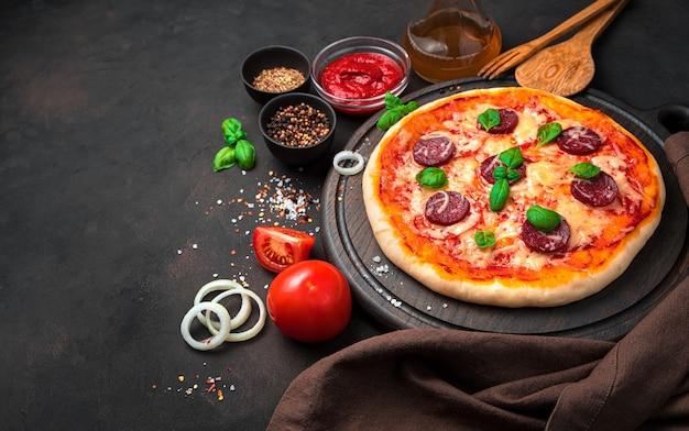 Pizza z salami, serem i pomidorami na brązowym tle betonu.