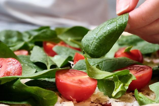 Pizza z serem, pomidorami, szpinakiem i wędzoną kiełbasą